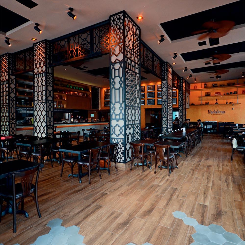 Bar em Goiânia mescla cores quentes e jardim vertical na fachada