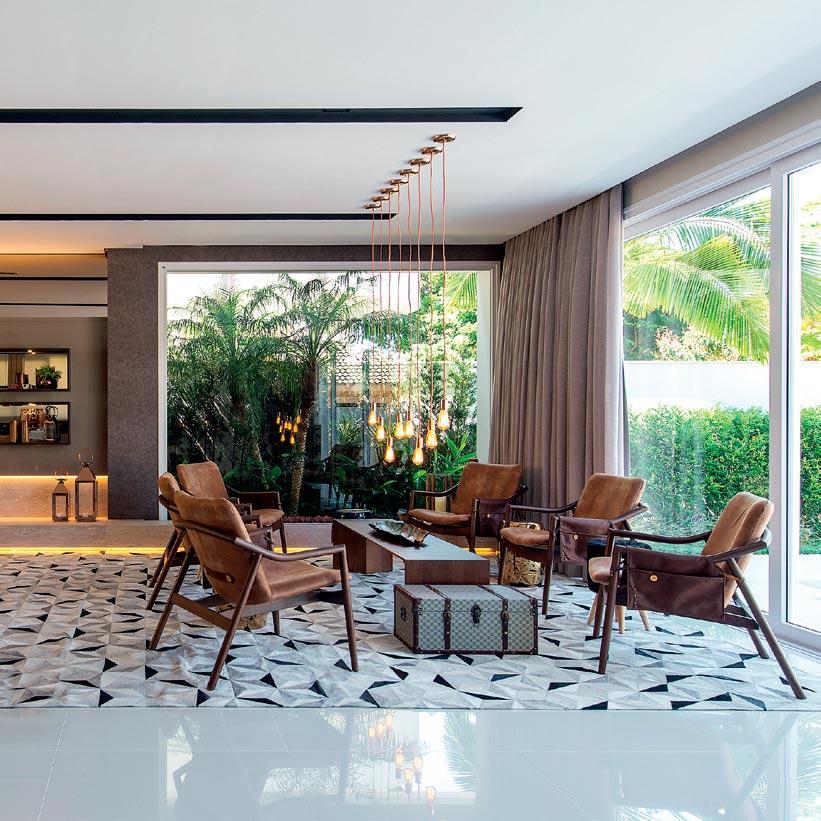 Mobiliário, gesso e iluminação marcam as divisões desta casa