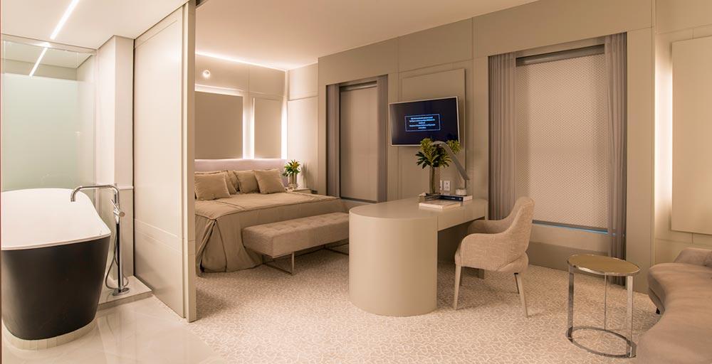 Suíte de hotel tem banheira no quarto e décor em tons neutros