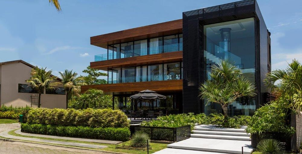 Casa com fachada de vidro privilegia a vista para a praia