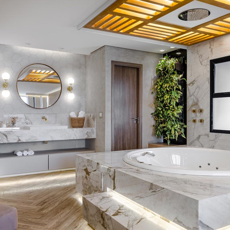 Suíte de 90 m² conta com banheira ao lado da cama