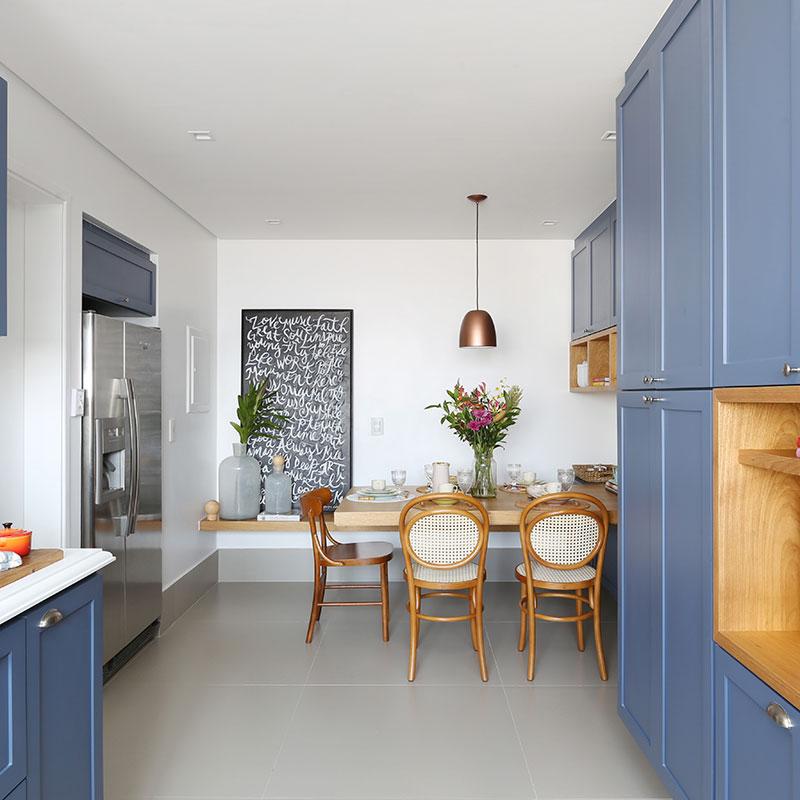 Cozinha tem móveis azuis e mesa em balanço