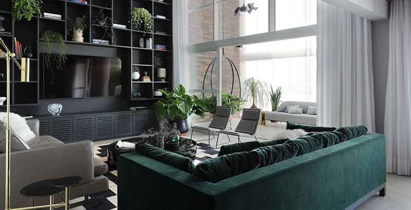 Estante personalizada, jardim vertical e muito verde compõem o décor deste apê