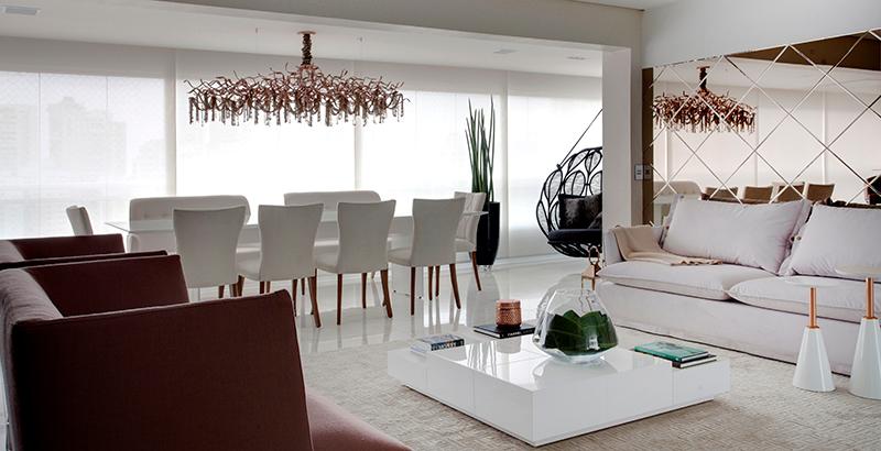 Varanda de apartamento abriga sala de jantar, bar e balanço