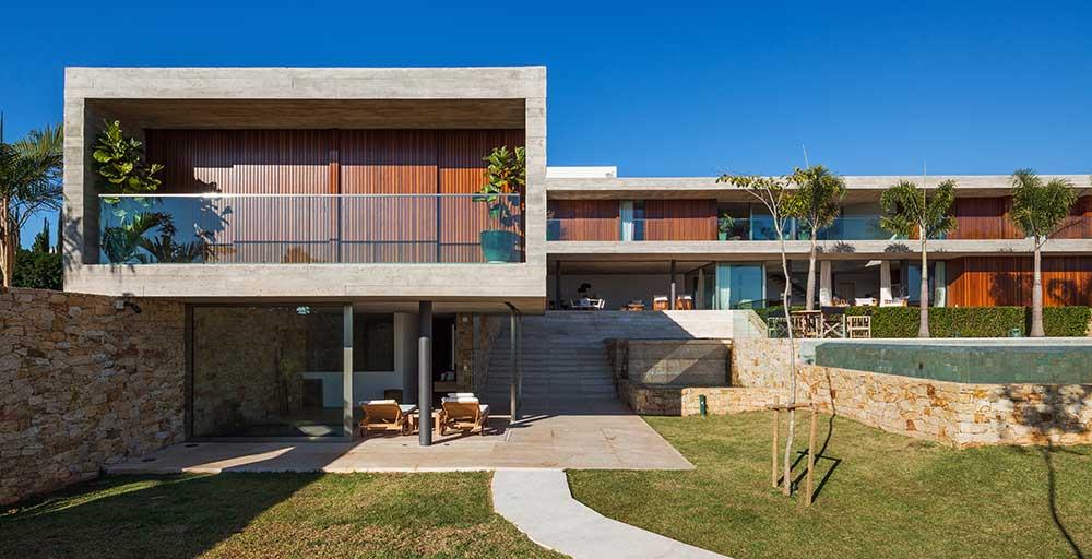 Diferentes volumes setorizam os ambientes e driblam o terreno irregular desta casa no interior de São Paulo