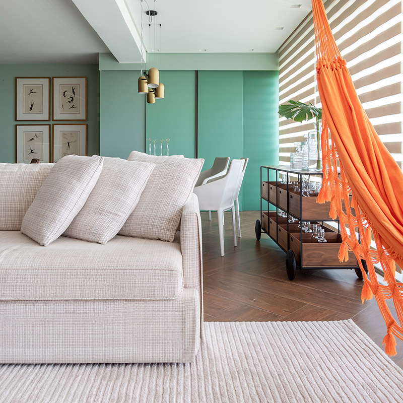 Apê na Bahia tem paredes verdes e uma rede na sala de estar