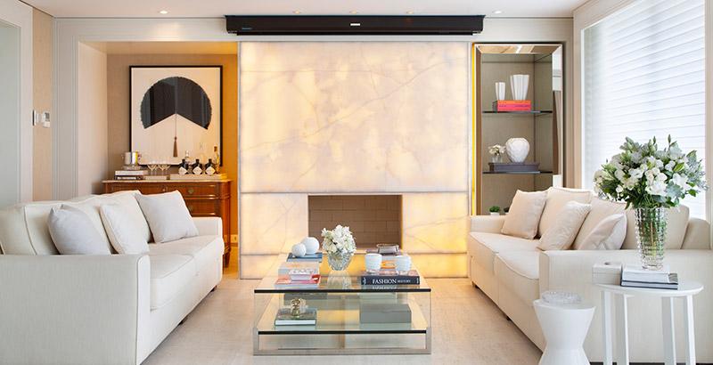 Apartamento com décor neutro possui lareira com iluminação embutida